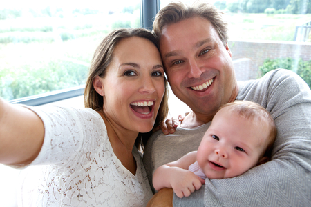 Close up portrait of a happy couple taking a selfie with baby photo