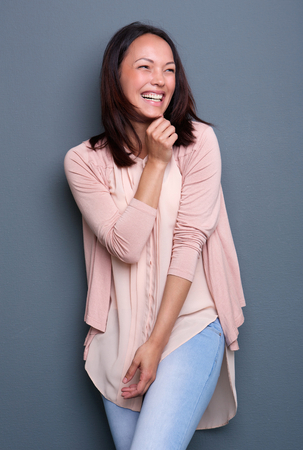 woman pose: Portrait of a joyful young woman laughing on gray background Stock Photo