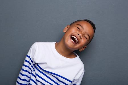회색 배경에 웃는 행복 어린 소년의 초상화를 닫습니다