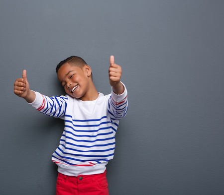 Portrait of a cute little boy smiling with thumbs up sign on gray background Imagens