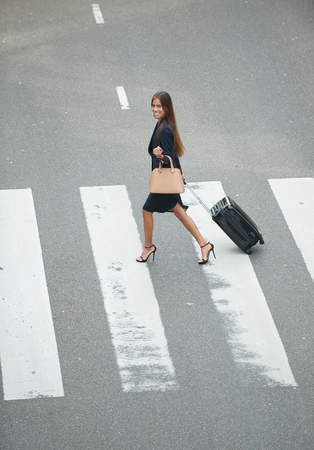 crossway: Portrait of a business woman crossing at zebra crossway with travel bags Stock Photo