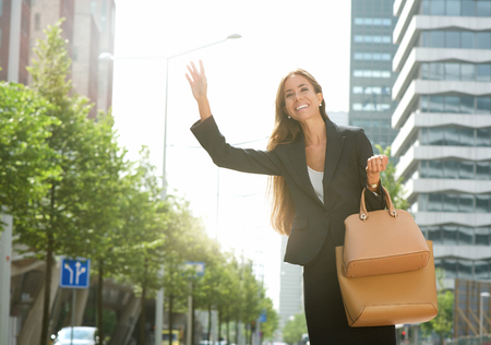 Portrait of a businesswoman raising arm for taxi in the city photo
