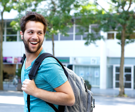 smiling man: Close up portrait of a smiling man walking with bag outdoors Stock Photo