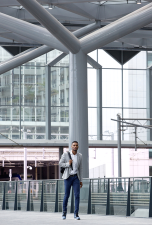 Full length portrait of an african man walking alone at airport photo