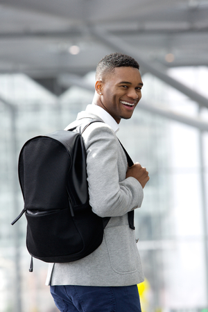 Portrait of a young black man smiling with bag at airport photo
