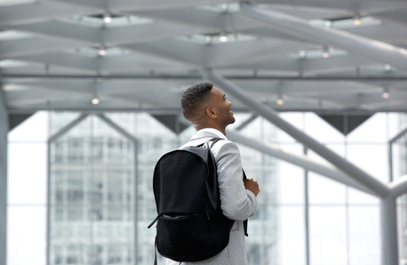 Rear view portrait of a young man smiling with bag at airport  photo