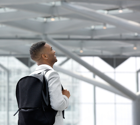 Portrait from behind of a young black man at airport with bag photo