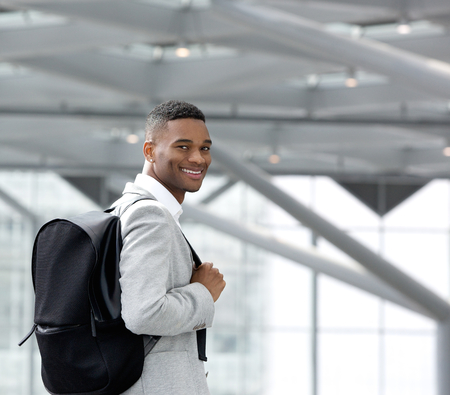 Close up portrait of a handsome young black man smiling with bag photo