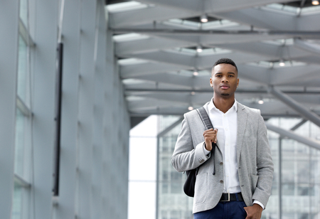 Portrait of a cool young man walking inside station building with bag photo
