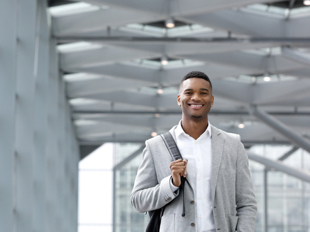 Close up portrait of an african american man smiling with bag at airport photo