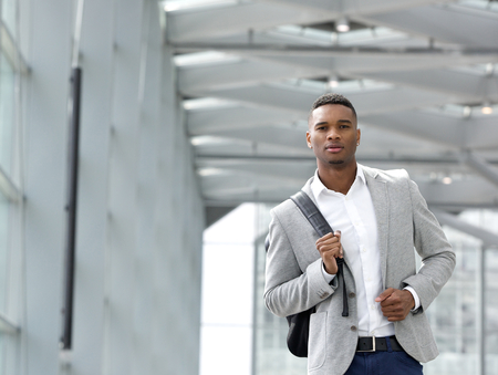 Close up portrait of an attractive young man walking with bag photo