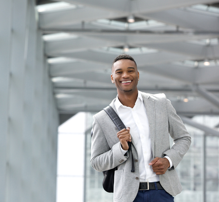 Close up portrait of a cheerful young man walking at airport with bag photo