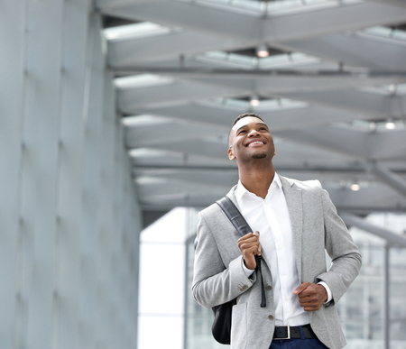 Close up portrait of a happy young man with bag at airport photo