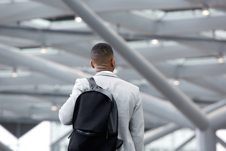 Rear view portrait of a black man standing in airport with bag
