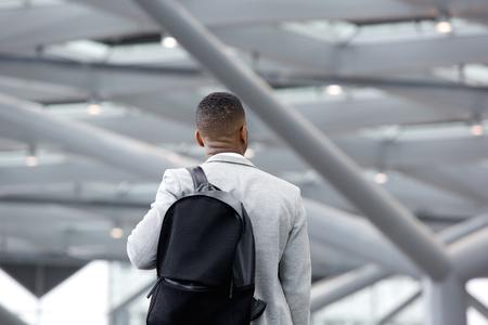 personas de espalda: Vista trasera retrato de un hombre negro de pie en el aeropuerto con el bolso