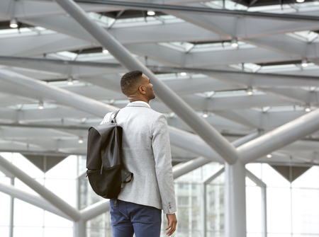 Portrait from behind of a black man standing alone in airport with bag photo
