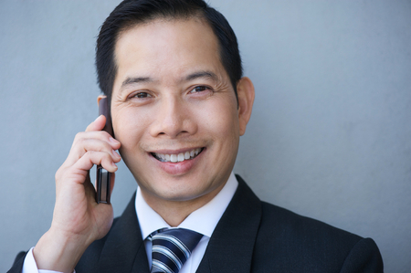 asian business people: Close up portrait of an asian businessman smiling with mobile phone