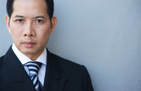 face expressions: Close up portrait of a smart businessman on gray background Stock Photo