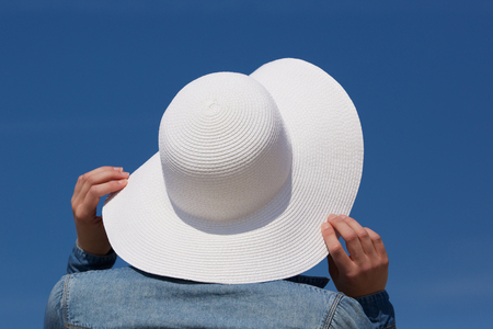 travel backgrounds: Close up portrait of a woman holding white sun hat from behind Stock Photo