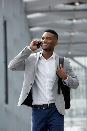 Close up portrait of a cheerful young man talking on mobile phone photo