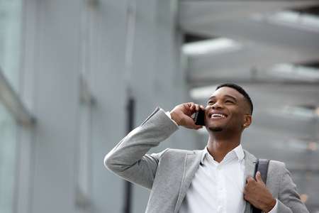 Close up portrait of a happy young man talking on mobile phone inside building photo