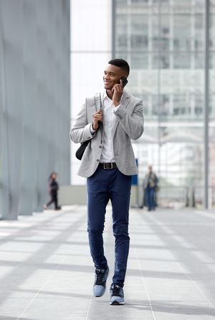 Full length portrait of a happy young man walking and talking on mobile phone Stock Photo