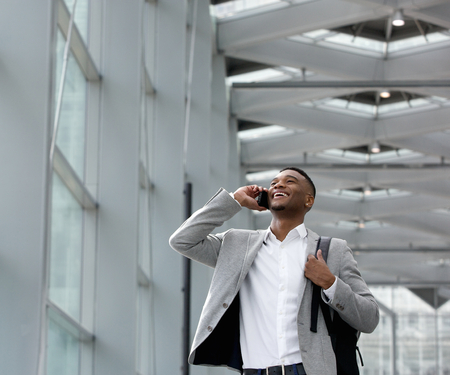 Close up portrait of a young businessman smiling and calling by mobile phone inside building photo