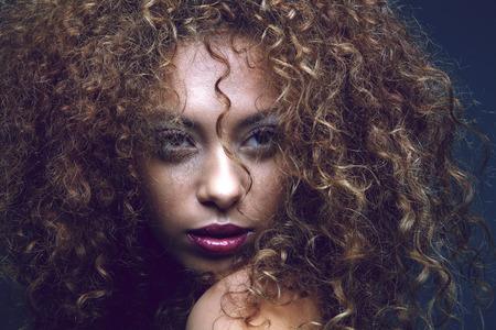 brown hair blue eyes: Close up portrait of a sensual black female fashion model