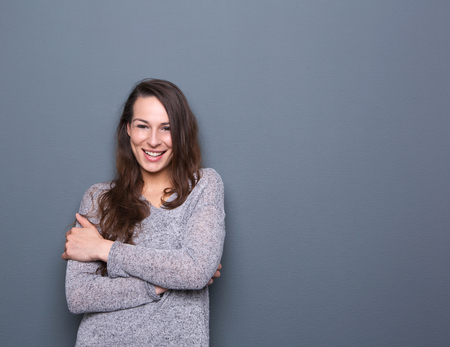 Portrait of a cheerful young woman smiling with arms crossed on gray background photo