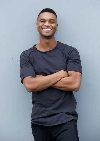 Portrait of a friendly black man smiling with arms crossed against gray background  Imagens