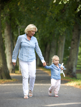children walking: Portrait of a happy grandmother walking with baby girl in park Stock Photo