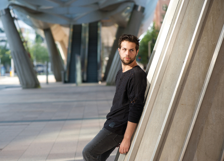 Side view portrait of a handsome male fashion model standing outdoors photo