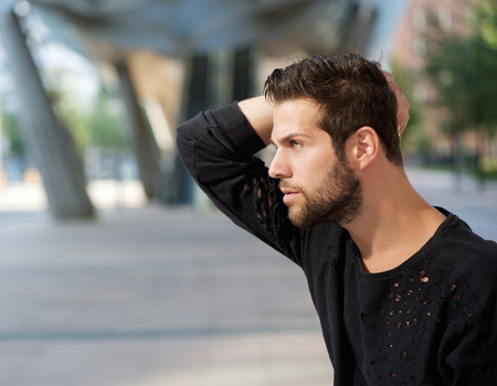 Close up side view portrait of a male fashion model posing with hand in hair photo