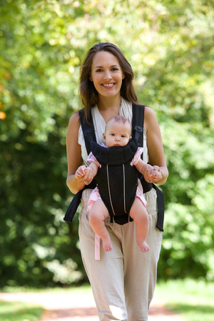 Portrait of a happy mother walking with infant in baby carrier   photo