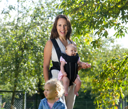 baby carrier: Portrait of a happy mother smiling with her two baby daughters