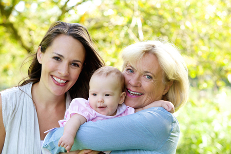 Close up portrait d'une grand-mère et la mère souriante avec bébé
