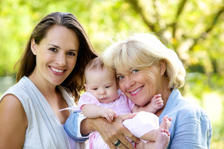 Portrait of a mother and grandmother smiling with baby outdoors