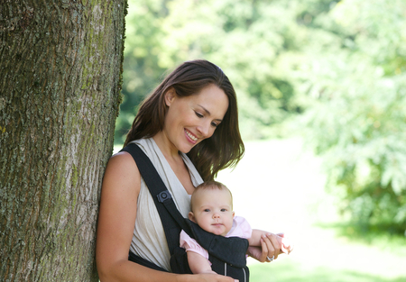 baby carrier: Portrait of a smiling mother with cute baby in sling
