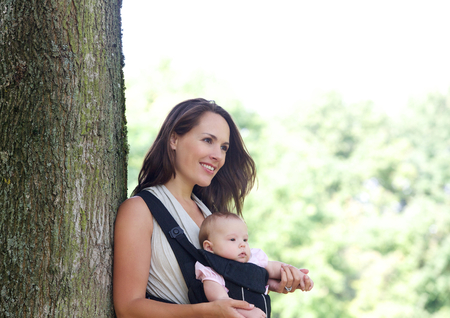 baby carrier: Portrait of a mother smiling with infant in baby carrier