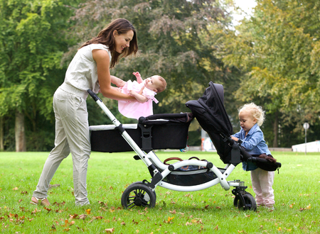 Portrait of a mother and daughters with pram outdoors