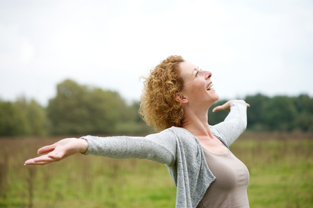Close up portrait of a cheerful carefree woman with arms outstretched Stockfoto
