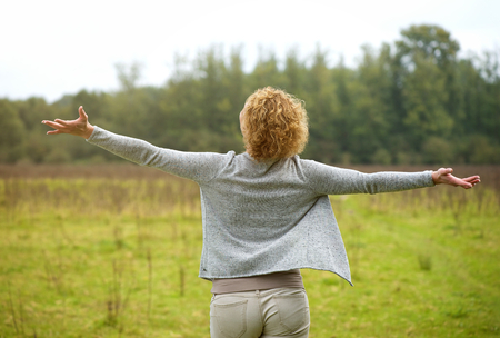 Portrait of the back of a carefree woman with arms spread open outdoors