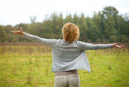 personas de espalda: Retrato de la parte posterior de una mujer despreocupada con los brazos extendi� abiertos al aire libre