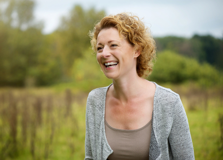 mid life: Close up portrait of a smiling middle aged woman outdoors