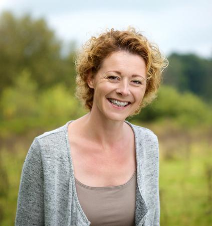 Close-up portret van een mooie rijpe vrouw lachend in het park Stockfoto