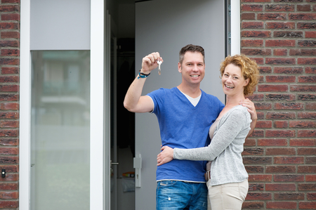 Portrait of a happy couple smiling outside new home holding keys photo