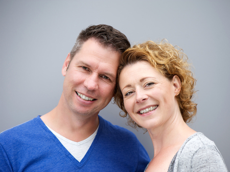 close portrait: Close up portrait of a middle aged couple smiling against gray background Stock Photo