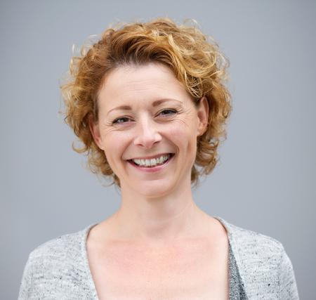 Close-up portret van een mooie vrouw lachend op een grijze achtergrond