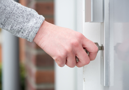 Close up side view female hand inserting key in door Stockfoto