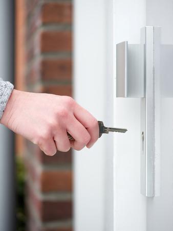 tecla enter: Vista lateral llave de retención mano femenina para insertar en la cerradura de puerta Foto de archivo